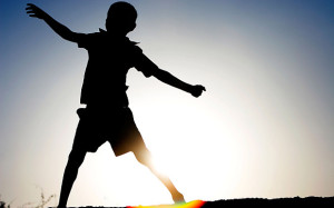 Silhouette profile of a young Indian boy dancing against hazy sun setting background showing lens flare. Image shot 2007. Exact date unknown.